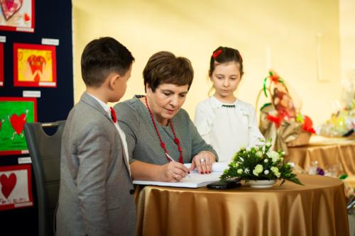 Podlaski Kurator Oświaty Pani Beata Pietruszka podpisuje się w księdze pamiątkowej w obecności dzieci.