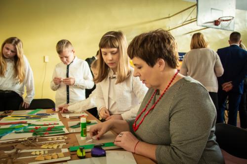 Podlaski Kurator Oświaty Pani Beata Pietruszka wraz z dziećmi wykonuje prace plastyczną.