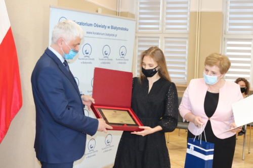 Na zdjęciu widoczny jest Wojewoda Podlaski Bohdan Paszkowski wręczający grawerton dla laureata konkursu. Po prawej stronie widoczna jest Pani Beata Pietruszka - Podlaski Kurator Oświaty.