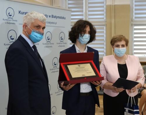 Na zdjęciu po prawej stronie widoczny jest Wojewoda Podlaski Bohdan Paszkowski. Na środku zdjęcia widoczny jest laureat konkursu z pamiątkowym grawertonem. Po prawej stronie widoczna jest Pani Beata Pietruszka - Podlaski Kurator Oświaty.