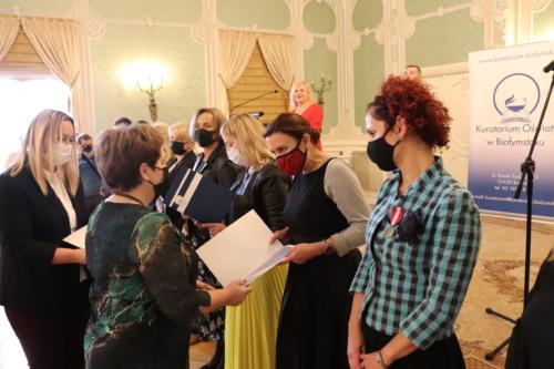Podlaski Kurator Oświaty Beata Pietruszka wręczająca nagrody kuratora nauczycielom.